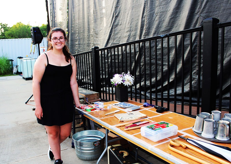 A volunteer helping with community theatre props at Leawood Stage Company's summer musical production of Kiss Me Kate near Kansas City