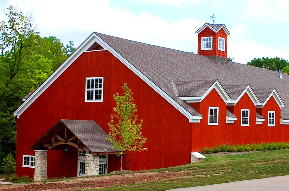 The large red barnwood building the Lodge at Ironwoods owned by Leawood Parks and Recreation near Kansas City where community theatre plays and musicals are held