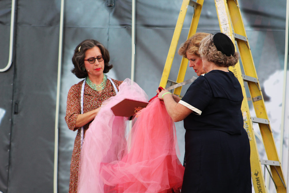 Three actors in our summer musical looking at Donated costumes and props to the Leawood Stage Company community theater near Kansas City